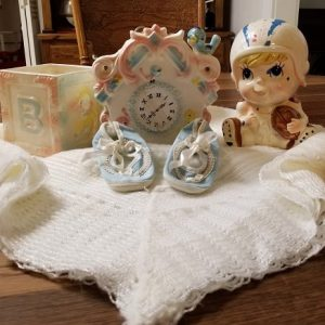 White baby blanket with blue booties and baby vases